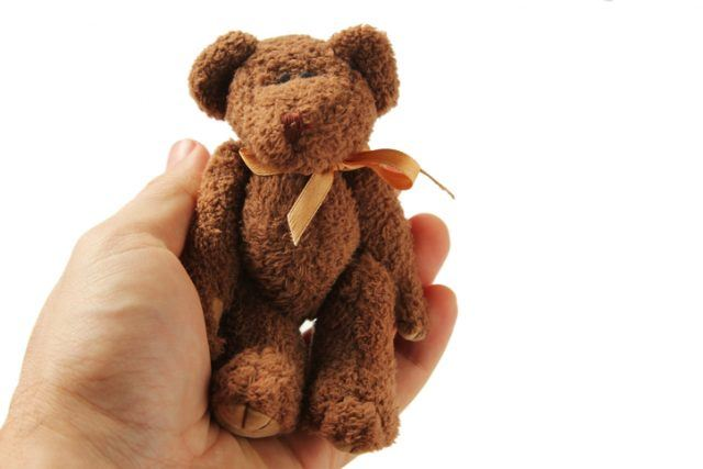 A hand holding a small brown teddy bear isolated on white background.