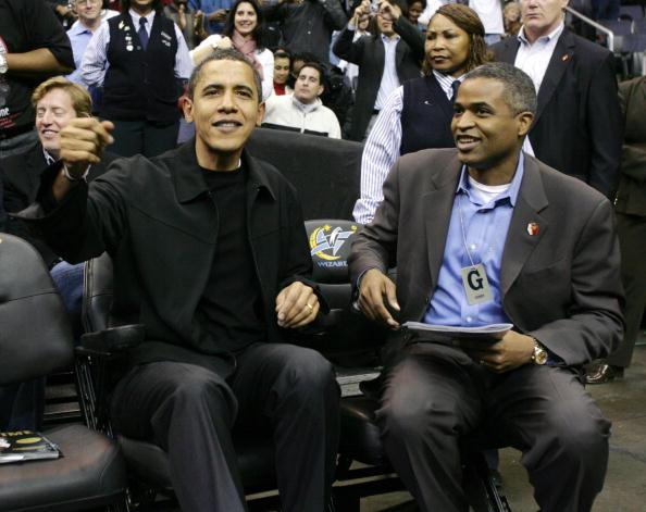 barack obama and marty nesbitt, both in black, watch a basketball game