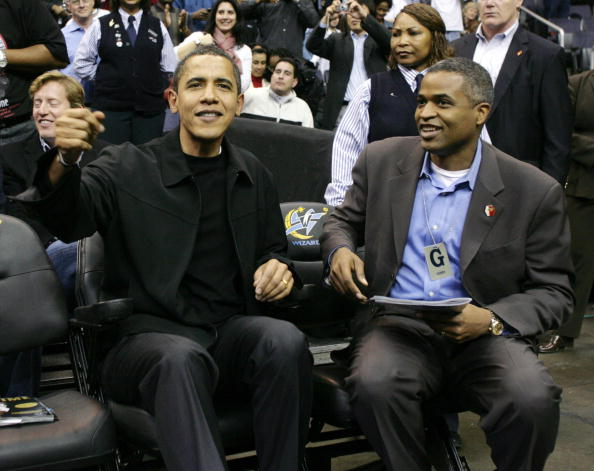 barack obama and marty nesbitt, both in black, watch a basketball game