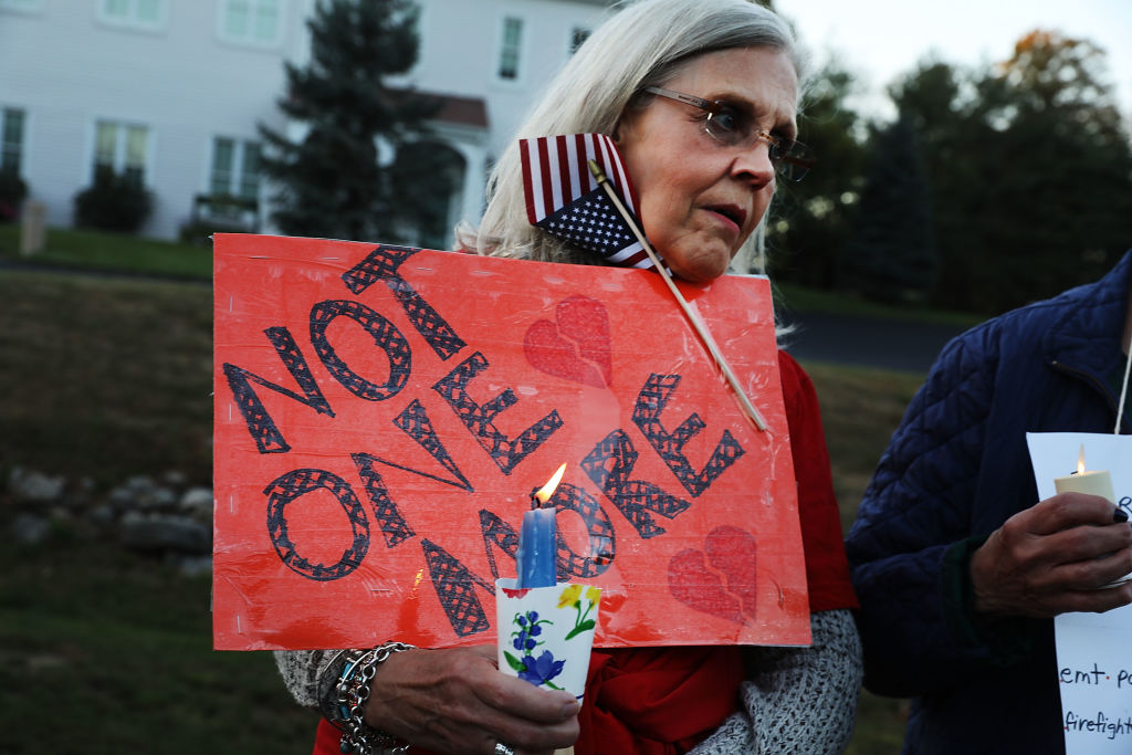 a woman holds a red sign and an American flag in a vigil against gun violence in newtown connecticut
