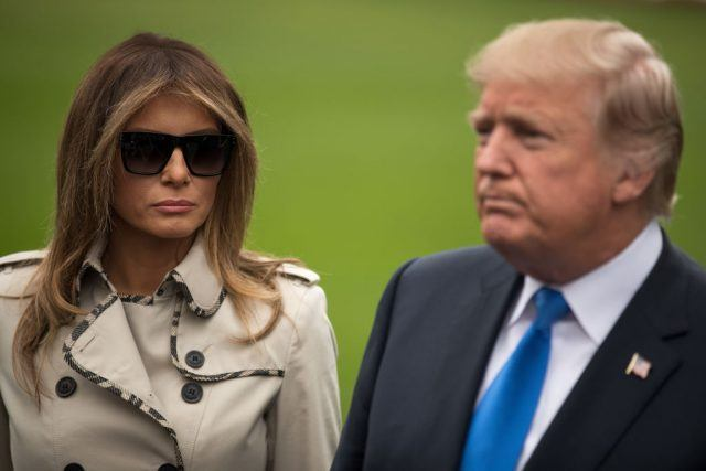 Donald and Melania Trump standing on a green lawn.