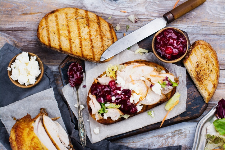 Homemade leftover thanksgiving day sandwich with turkey, cranberry sauce, feta cheese and vegetables. Top view