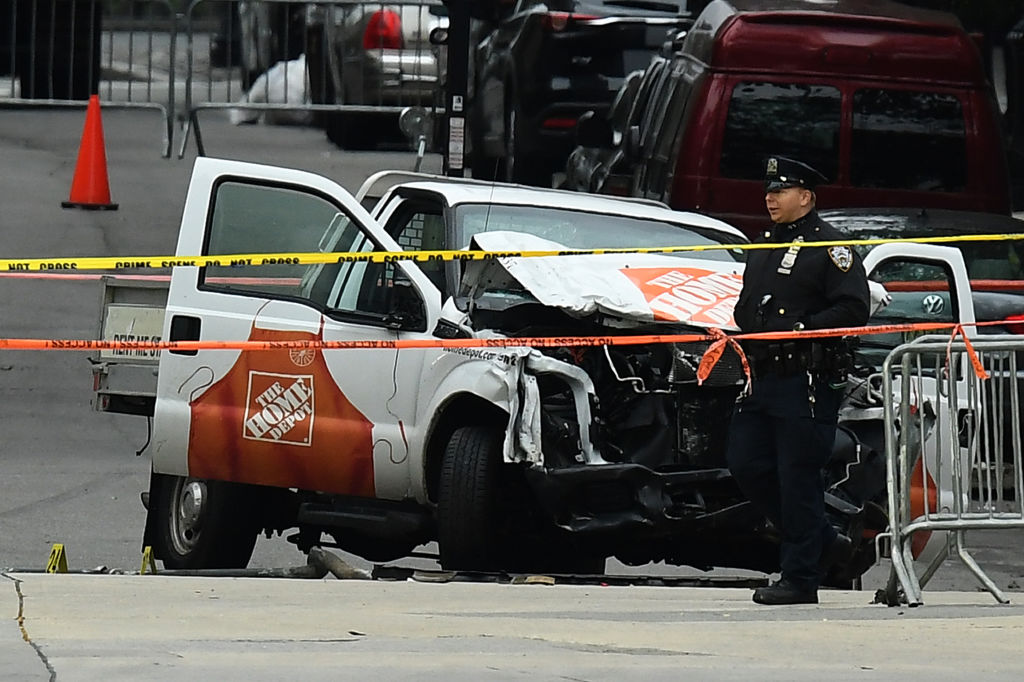 a mangled pickup truck with police tape and an officer in NYC