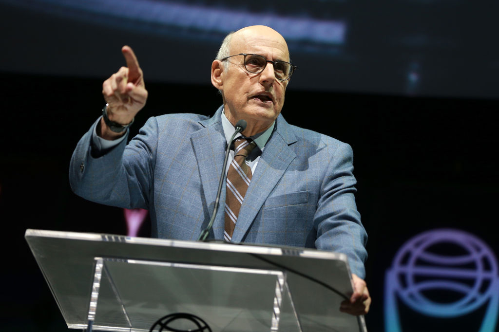 jeffrey tambor speaking at a podium in a light blue blazer