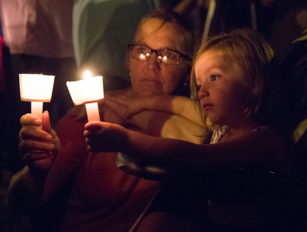 a child and a woman at a candlelight vigil in sutherland springs, texas