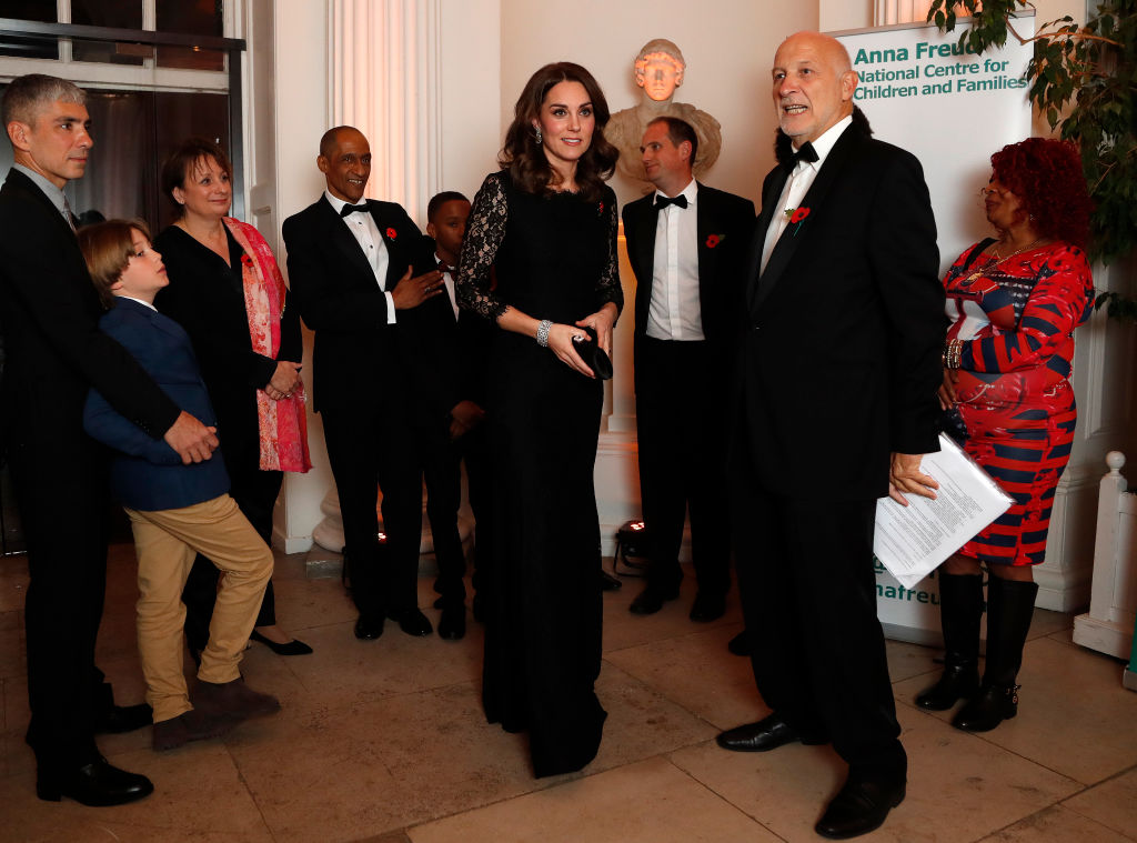 kate middleton in black talks to a man in a tuxedo