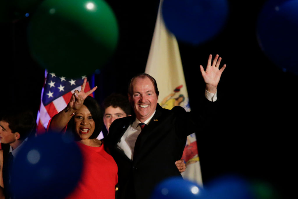 Phil Murphy celebrates his victory ina black suit while waiving at the crowd.