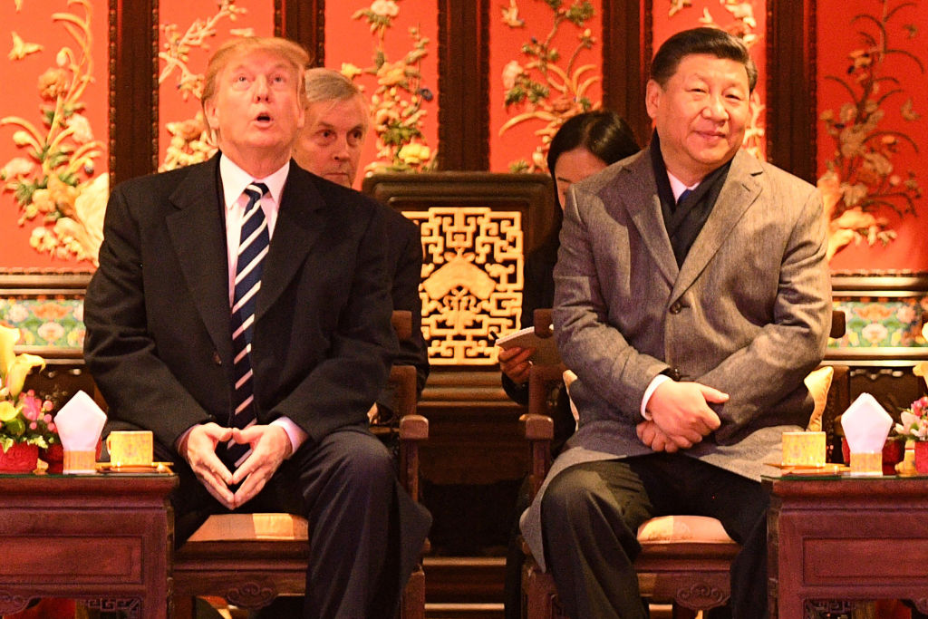 US President Donald Trump (L) looks up as he sits beside China's President Xi Jinping during a tour of the Forbidden City