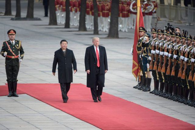 China's President Xi Jinping (2nd L) and US President Donald Trump review Chinese honour guards during a welcome ceremony at the Great Hall of the People in Beijing