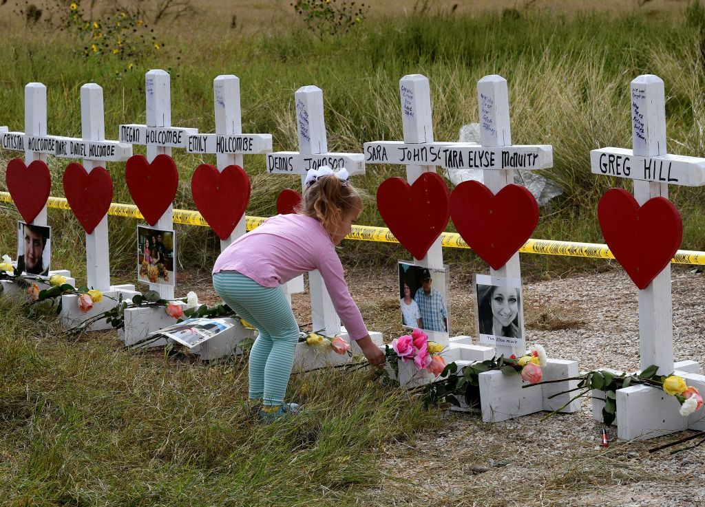 a child in a pink shirt leaves flowers next to a line of crosses with red hearts