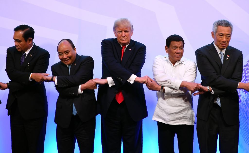 the asian leaders and trump grasp hands for a photo