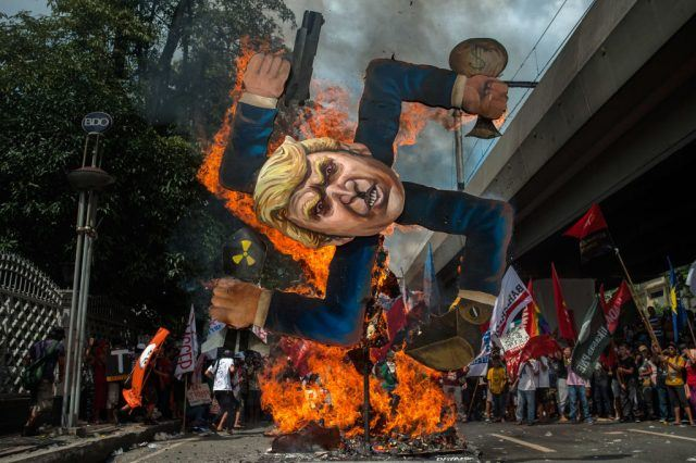 protesters burn an image of trump on a swastika