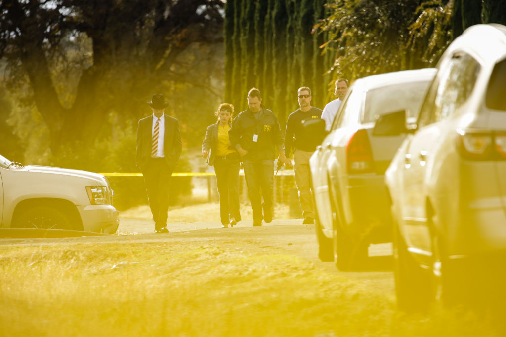 FBI agents, yellow caution tape, and police vehicles