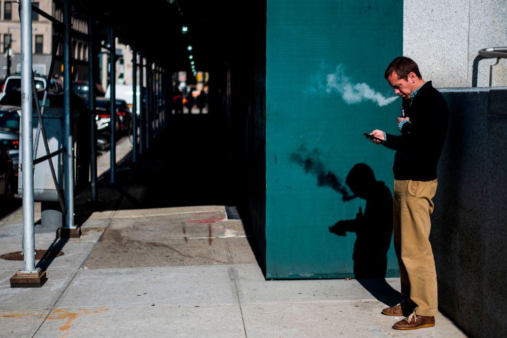 Man smoking on a sidewalk.