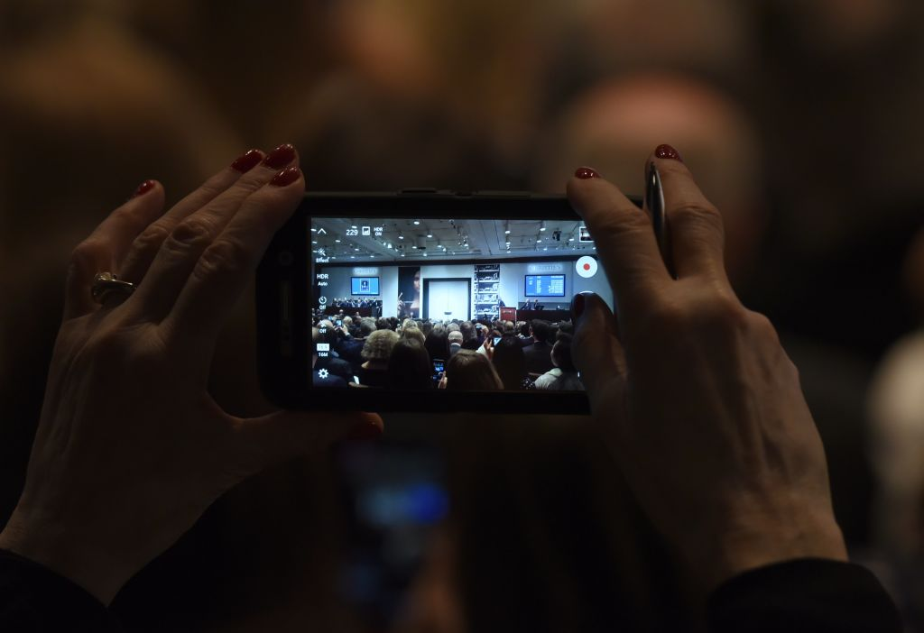 a woman takes a video on a cell phone in a darkened room