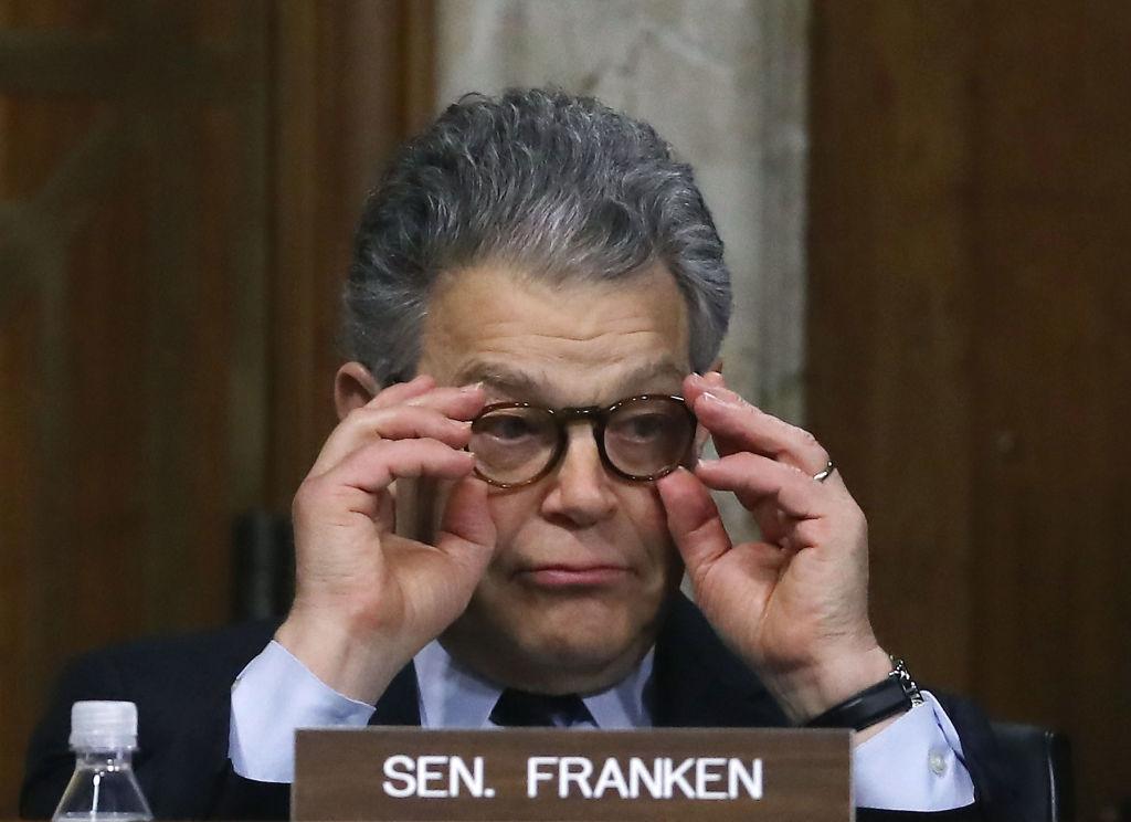 al franken adjusts his glasses behind his nameplate