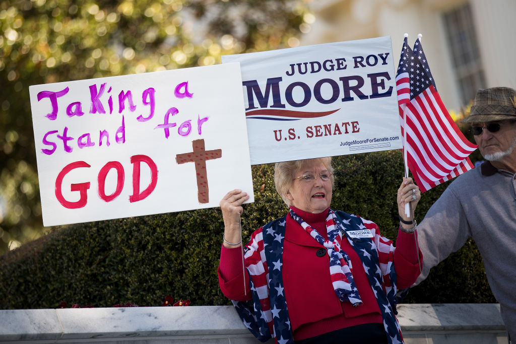 a woman holds pro-moore signs in alabama