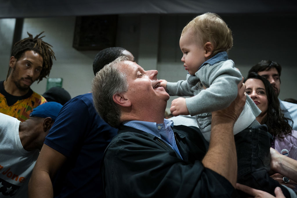 doug jones in blue lifting up a baby
