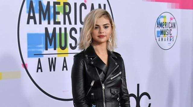 Selena Gomez stands on a red carpet in an edgy leather jacket.