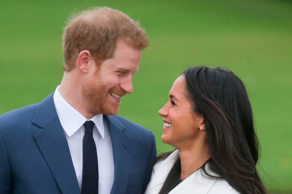 prince harry and meghan markle in a blue suit and white jacket smile at each other