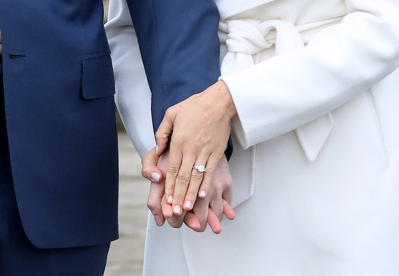 Prince Harry and actress Meghan Markle's hands, showcasing the engagement ring