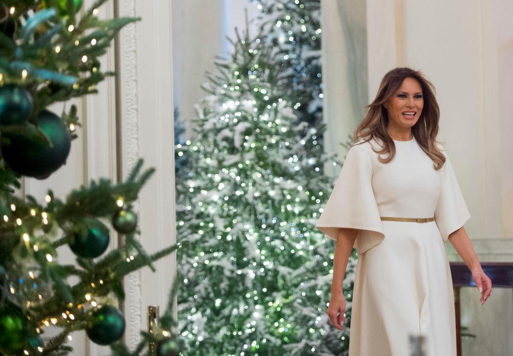 melania trump walks past a christmas tree
