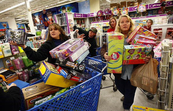 two women with loaded carts and their arms full wait in line during Black Friday
