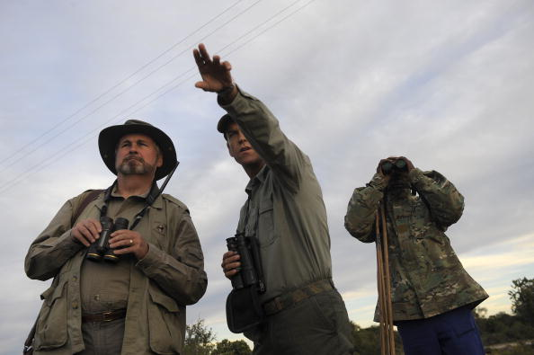 3 hunters survey the land in khaki vests