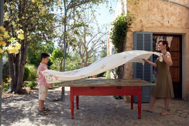 Son and mother throwing a tablecloth on the dinner table outside.