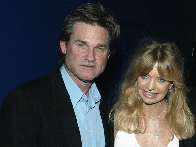 Goldie Hawn and Kurt Russel pose together in front of a blue wall.
