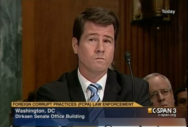 A man sitting in front of a microphone waiting to testify.