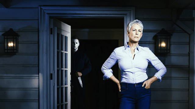 Jamie Lee Curtis stands in front of a dark house.