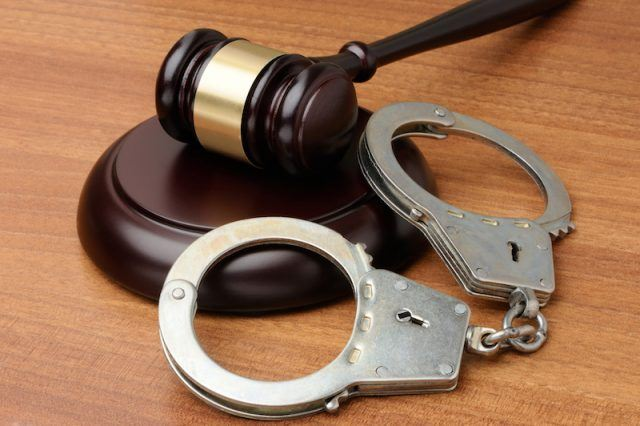 Handcuffs and gravel on a wooden desk.