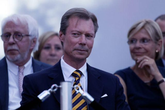 Grand Duke Henri of Luxembourg sits while listening to a speaker on stage.