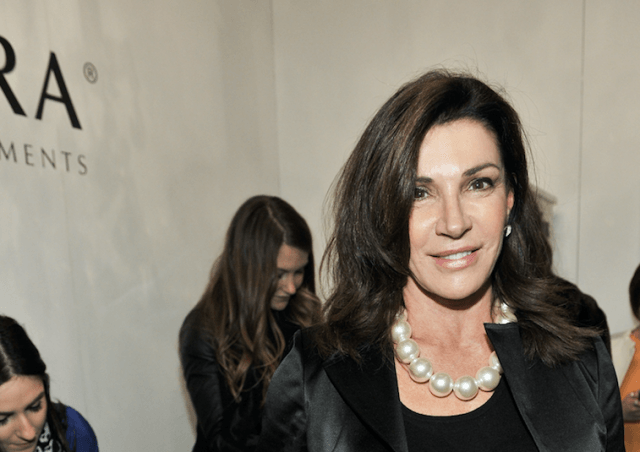 Hilary Farr stands at an event in black clothes and large pearls.