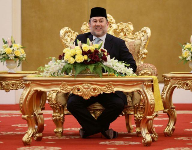 Sultan Muhammad V talks with Prince Charles while sitting in front of an elaborate gold throne.