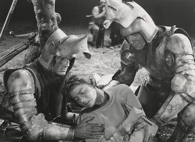 Joan being carried by two guards wearing armor.