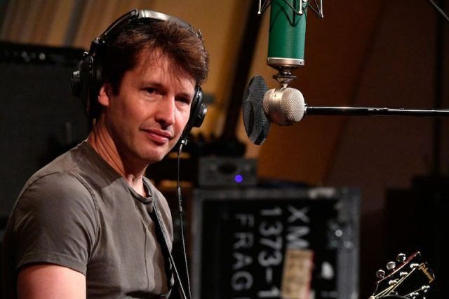 James Blunt in front of a microphone while wearing headphones.