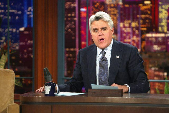 Jay Leno speaking behind a desk.