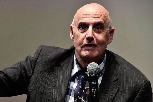 Jeffrey Tambor speaking in front of a microphone in a striped suit.