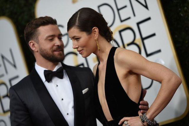 Justin Timberlake posing with his hand wrapped around Jessica Biel's back.