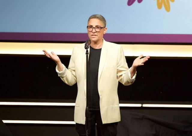 Jill Soloway stands in a yellow blazer while gesturing with her hands.