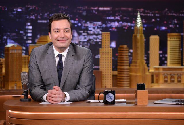Jimmy Fallon smiling behind a desk.