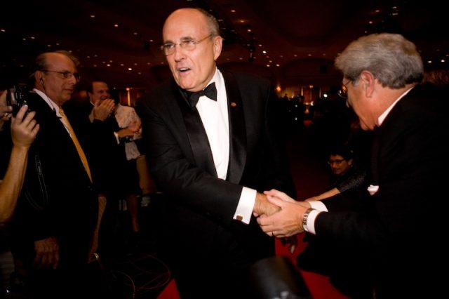 Rudolph W. Giuliani shakes hands with guests at a party.