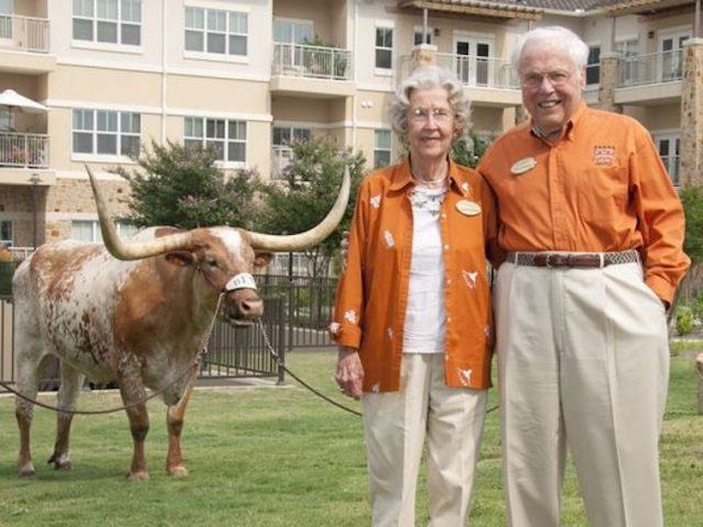 John and Charlotte Henderson stand behind a cow on a lawn.