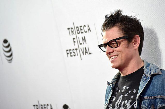 Johnny Knoxville smiling on the red carpet while wearing black glasses and a denim jacket.