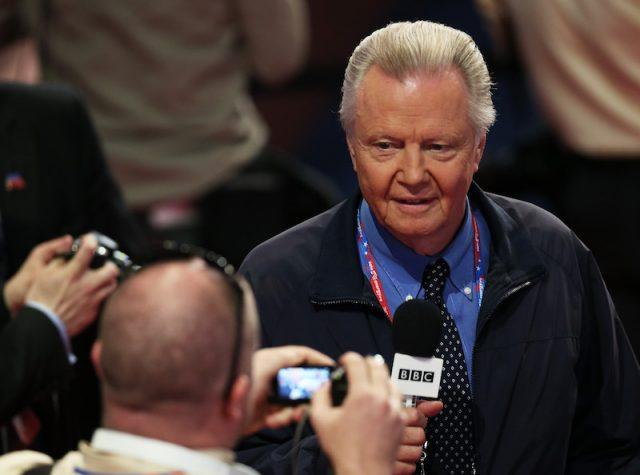 Jon Voight holding a microphone while reporting in front of cameras.