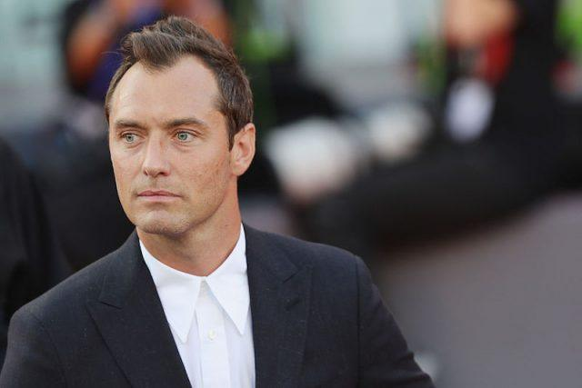 Jude Law standing on a red carpet while wearing a black suit and white shirt.