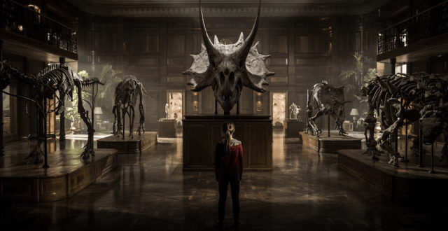 A young girl stands at a dinosaur museum.