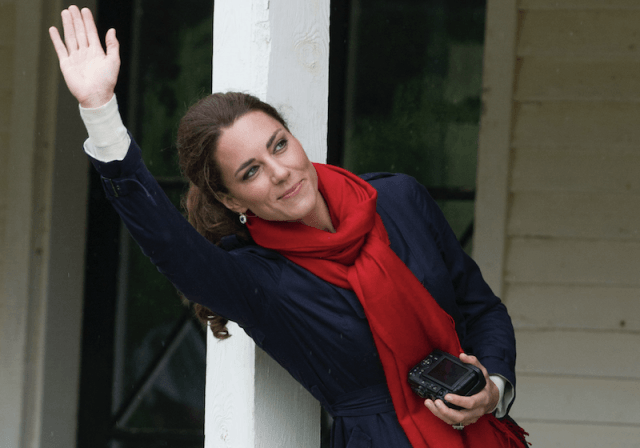 Kate Middleton waving and looking upwards while holding a camera.
